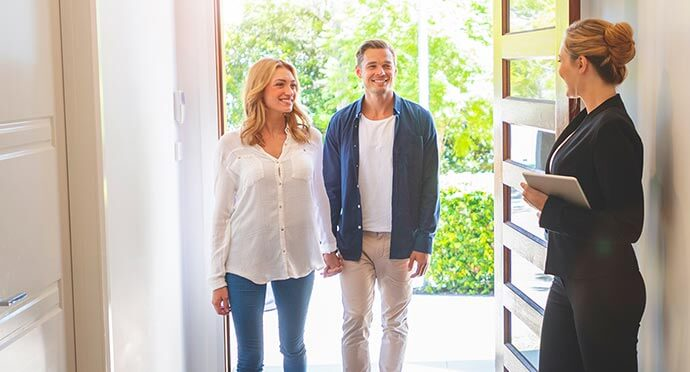 Property manager at door to investment property with couple